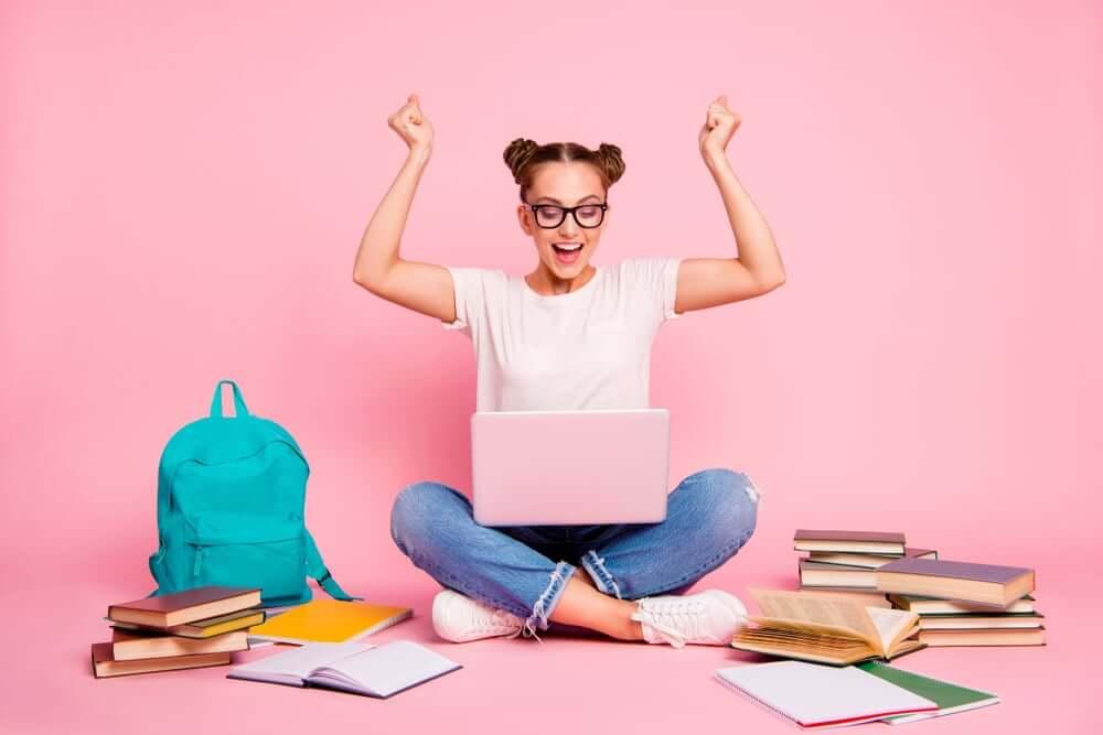女性が教材に囲まれて座り、パソコン画面を見て喜んでいる画像(勉強のイメージ)