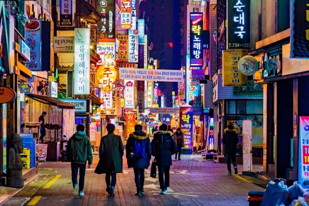 韓国の夜の街並みと歩く男性4人の後ろ姿